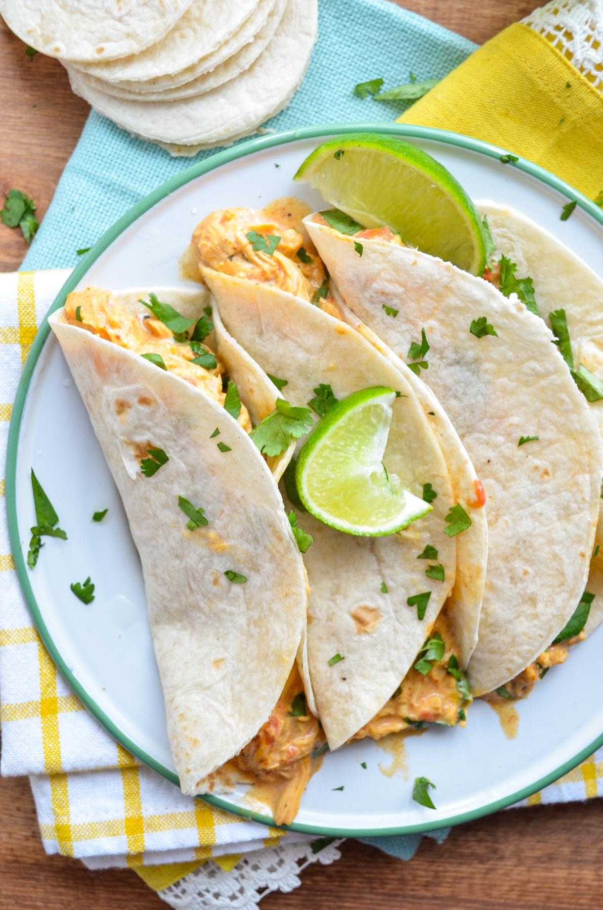 Three chicken queso tacos on a plate, resting on bright napkins.