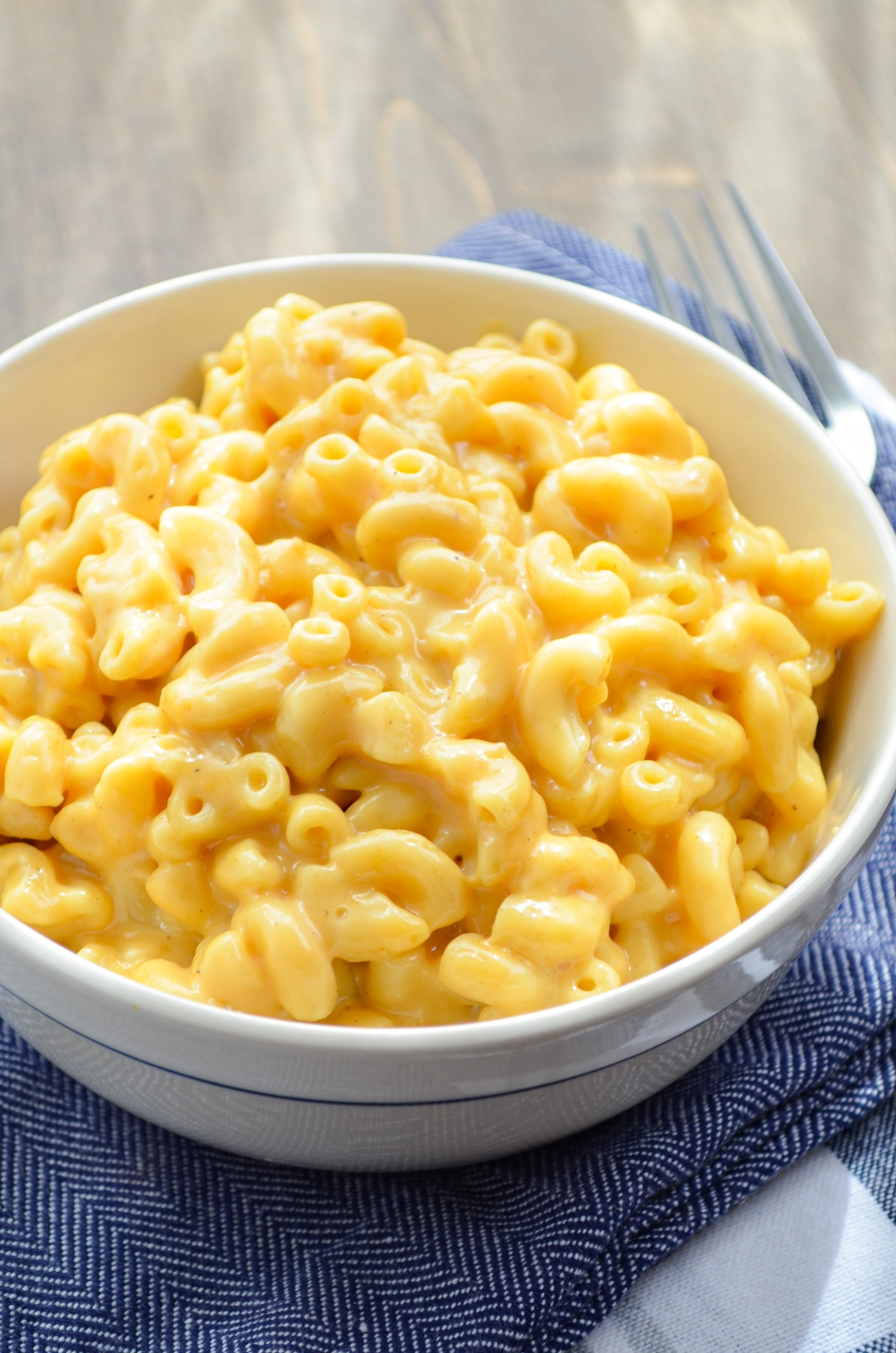 A bowl of macaroni and cheese, resting on blue napkins.
