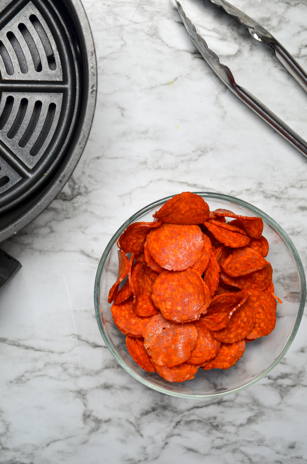 A bowl of pepperoni, with an air fryer basket and a pair of tongs on the side.