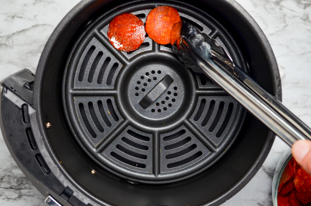 A set of tongs placing pepperoni slices in the basket of an air fryer.
