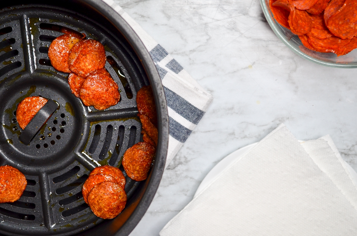 Air fryer pepperoni chips, fully cooked and ready to be drained on paper towels.
