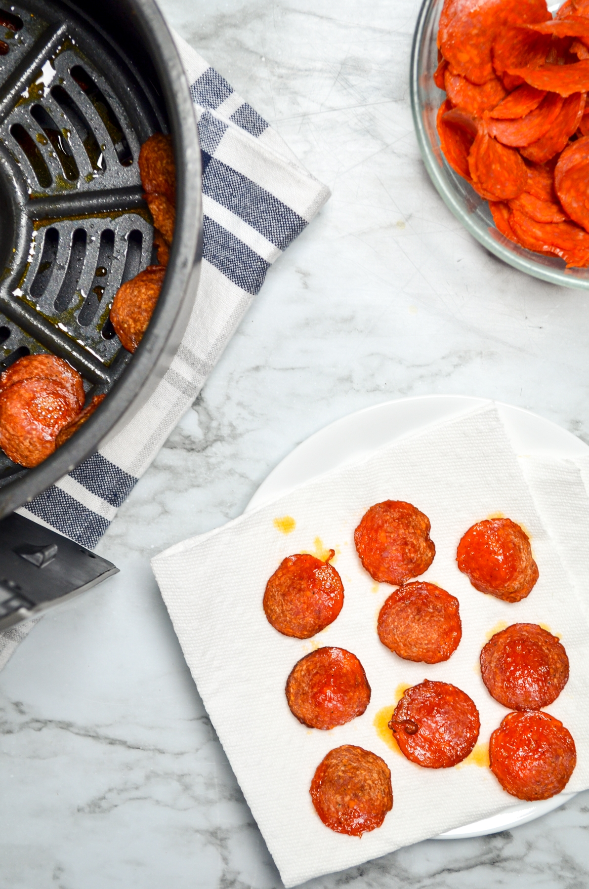 Air fryer pepperoni chips draining on paper towel to remove excess grease.