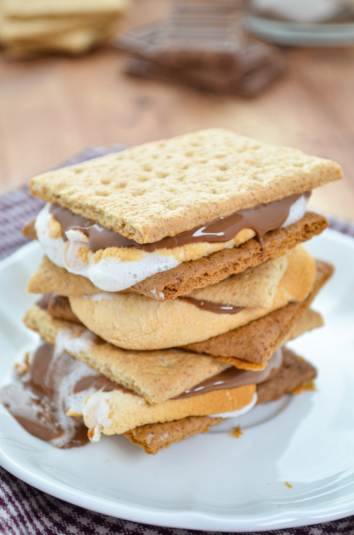 A stack of three s'mores on a white plate.