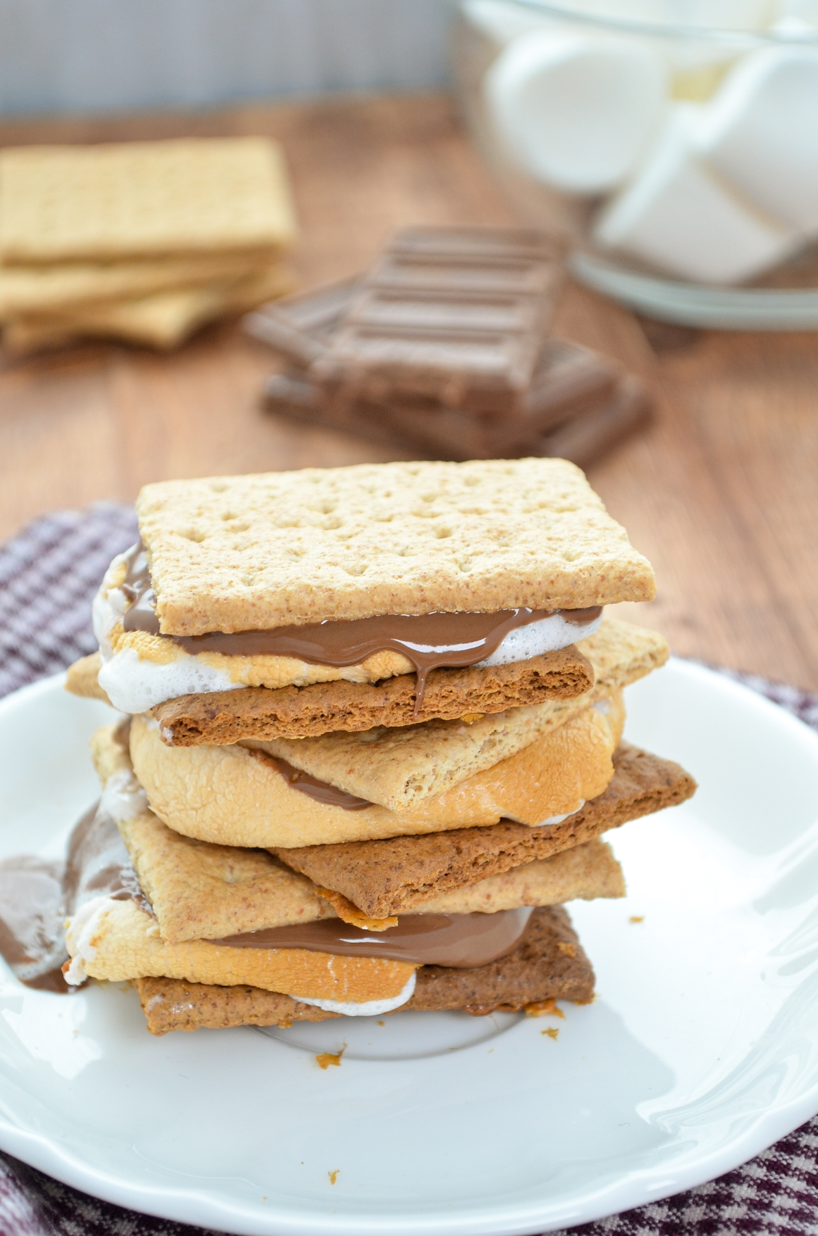 A stack of three s'mores with chocolate, marshmallows, and graham crackers in the background.
