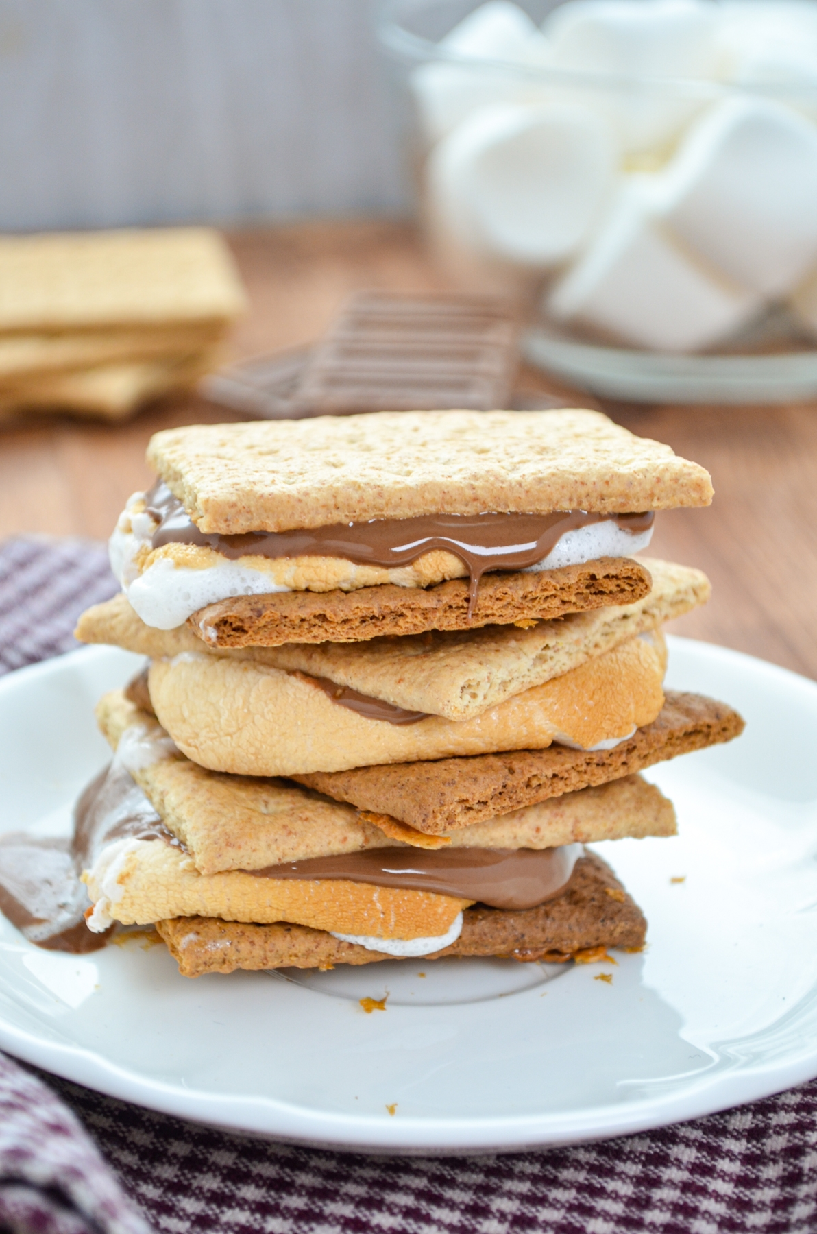 A stack of three smores on a small white plate.