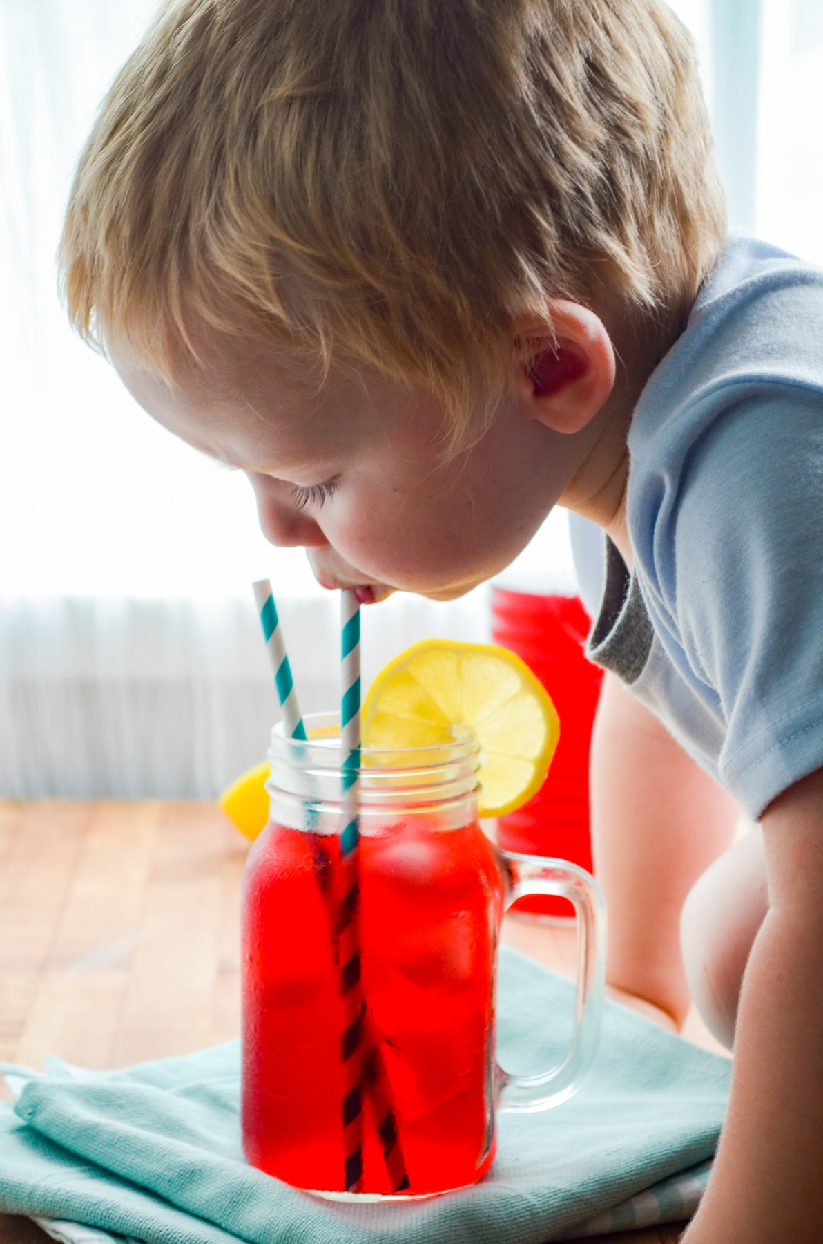 A toddler taking a sip of passion tea lemonade.