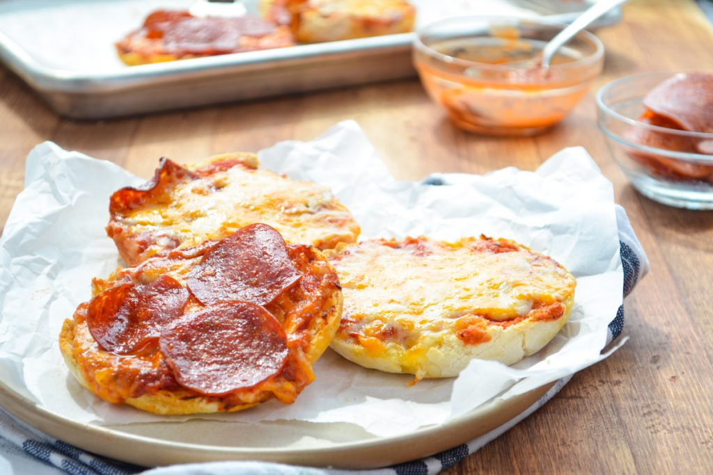 A plate of english muffin pizzas, with a prepared baking sheet full in the background.