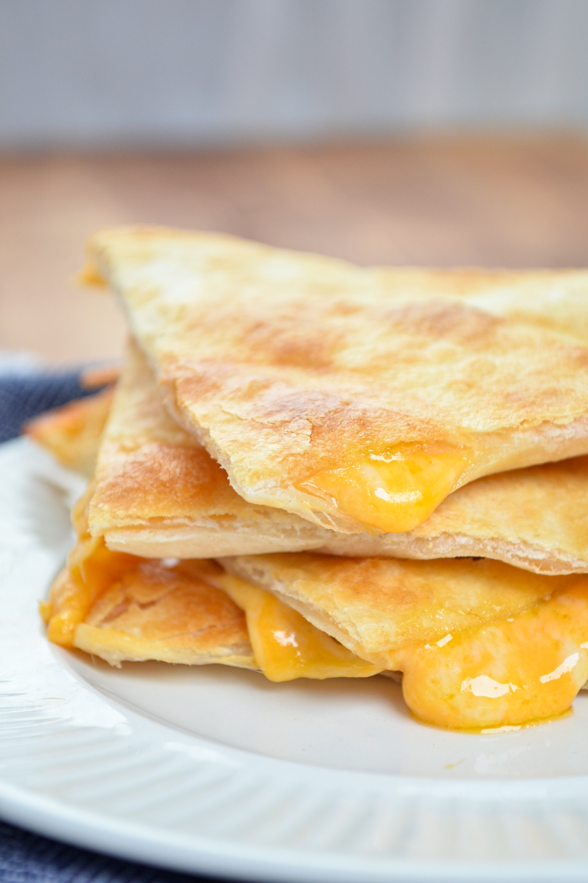 A stack of three air fryer cheese quesadilla triangles.