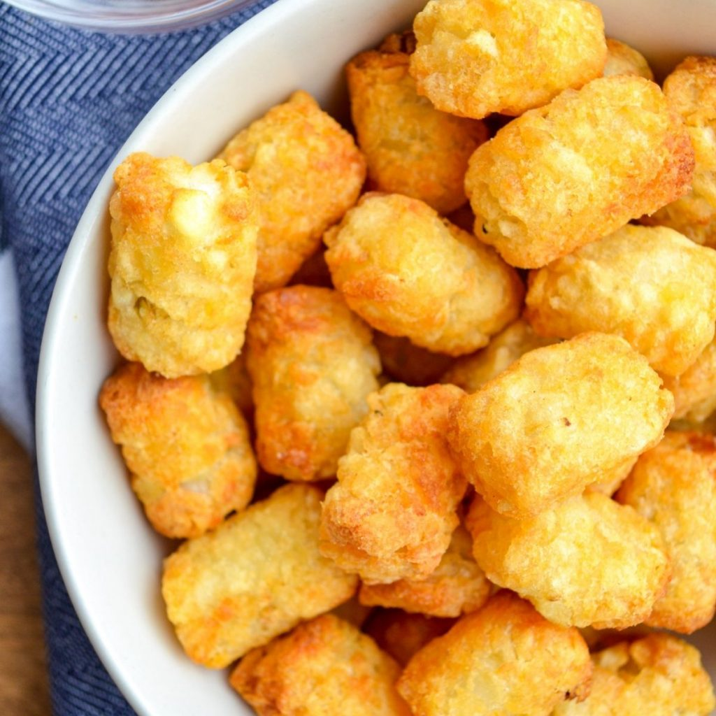 A bowl of cooked tater tots.