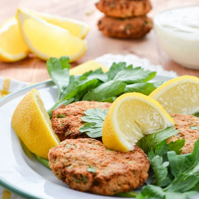 Salmon patties on a plate, garnished with parsley and lemon.