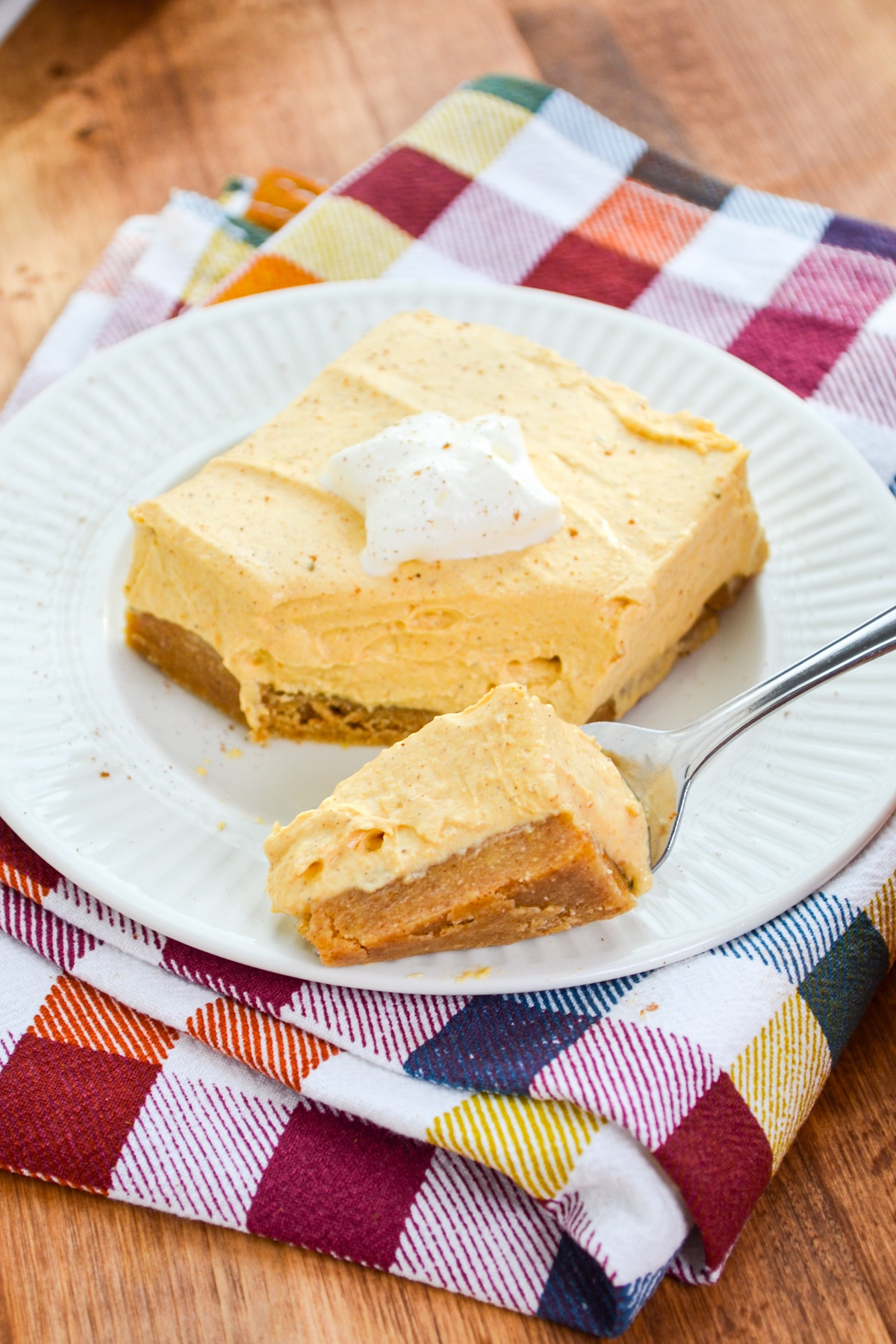 A fork taking a portion of some pumpkin cheesecake bars.