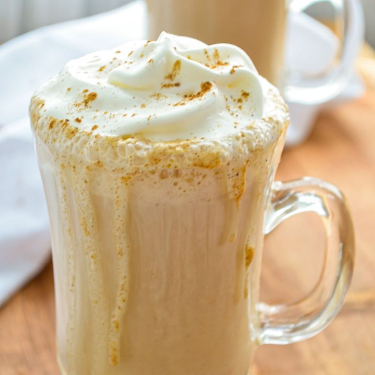 A glass mug filled with a pumpkin spice latte and covered with whipped cream.