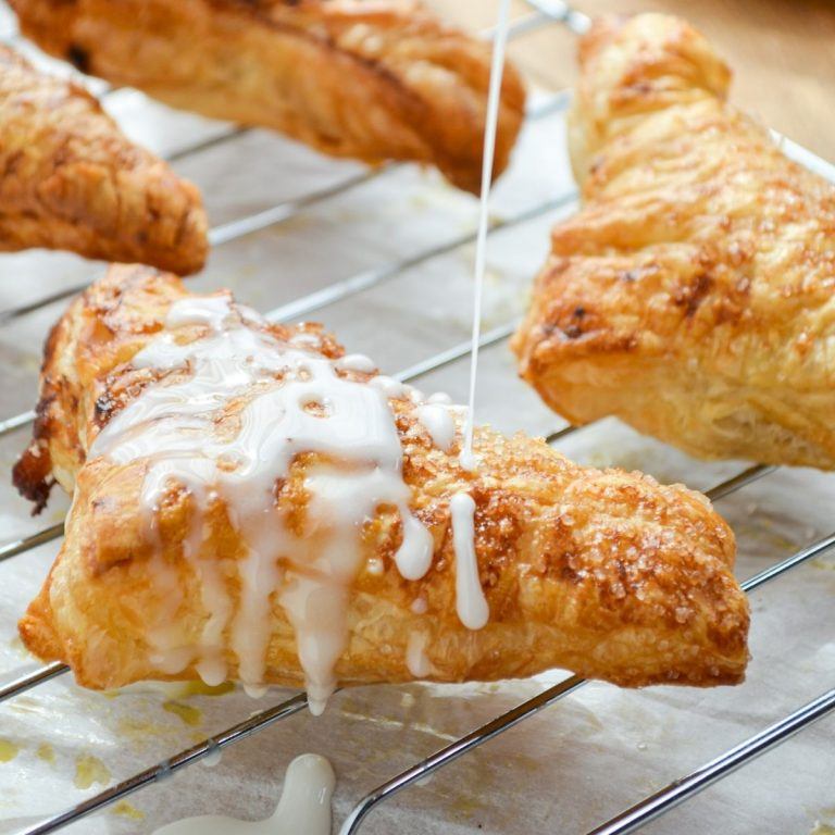 An apple turnover, being drizzled with a simple glaze.