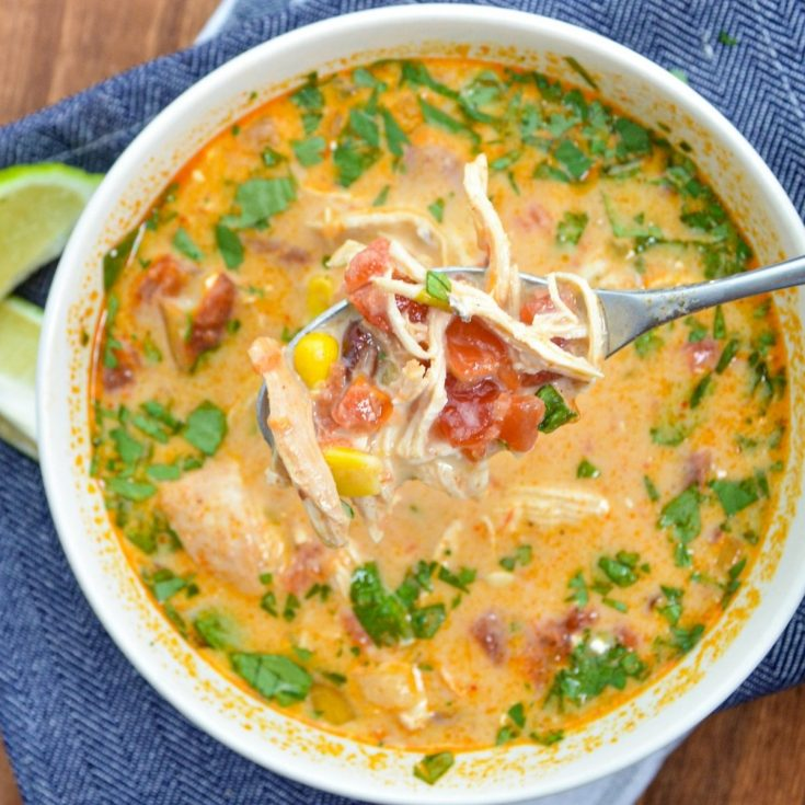 A bowl of creamy chicken tortilla soup, resting on blue napkins.