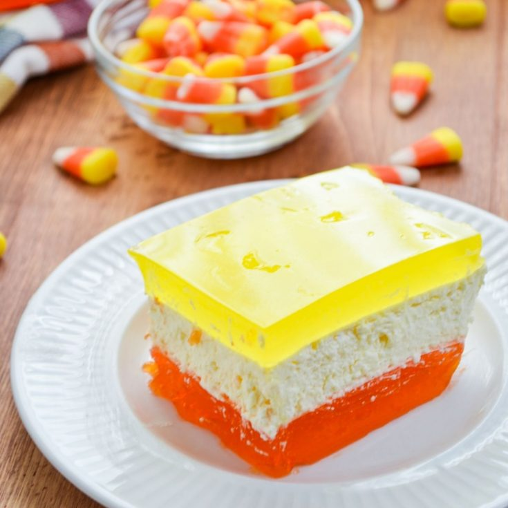 A jello dessert with three layers, using Halloween inspired colors. Orange, yellow, and white layers.