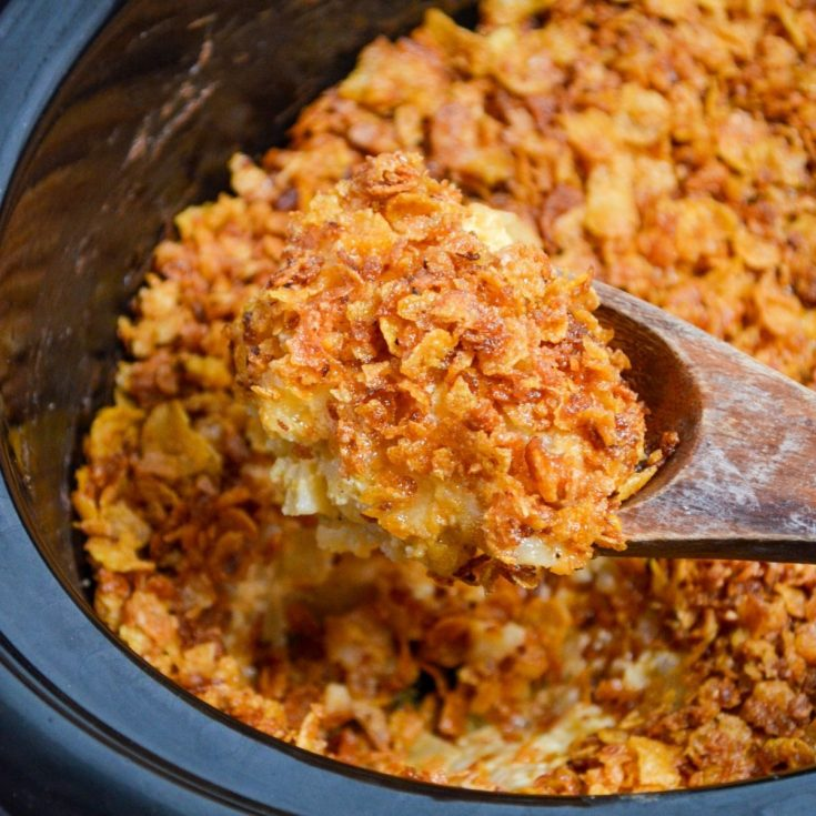 A large wooden spoon scoops up a portion of funeral potatoes made in a slow cooker.