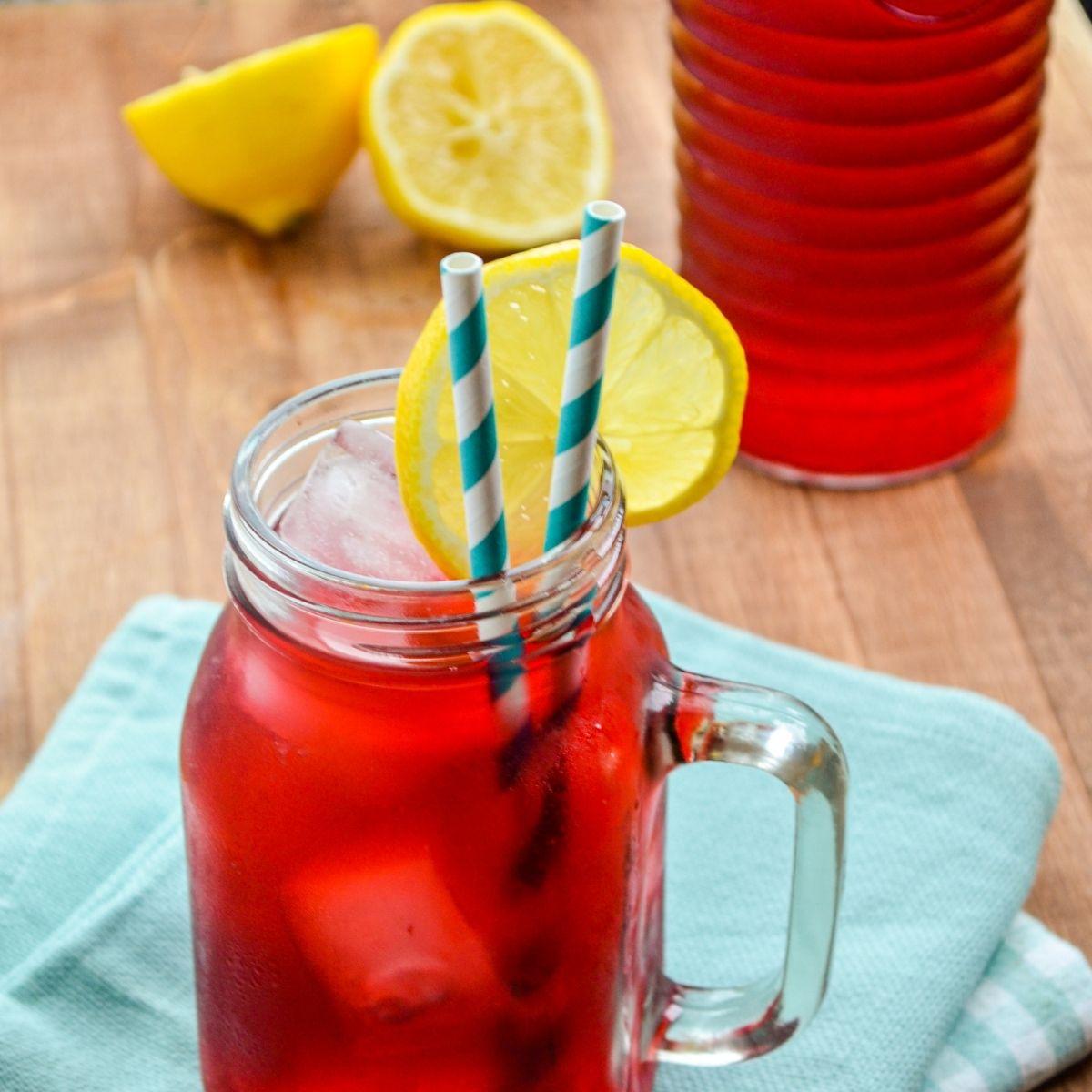 A glass of Passion Tea Lemonade, garnished with lemon wedges.