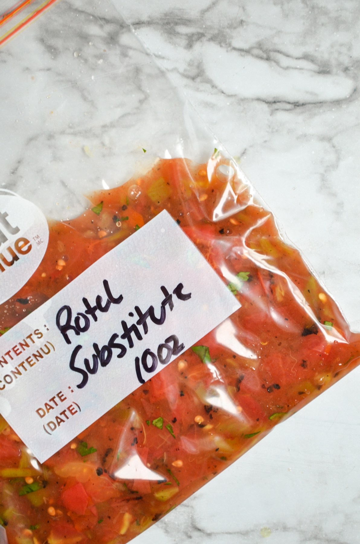 """A freezer baggie with green chilies and tomatoes inside. Labeled: """"Rotel substitute"""""""