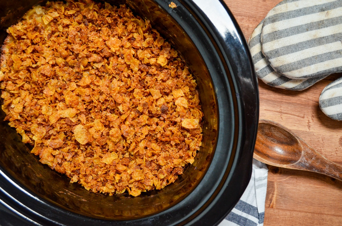 A crock pot of cheesy hasbrown casserole, topped with a crushed corn flake topping. A wooden spoon and oven mitts on the side.