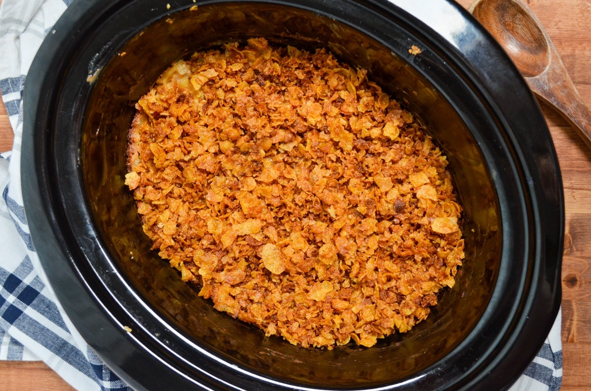 A slow cooker full of cheesy hashbrown potatoes, topped with crushed cornflakes.