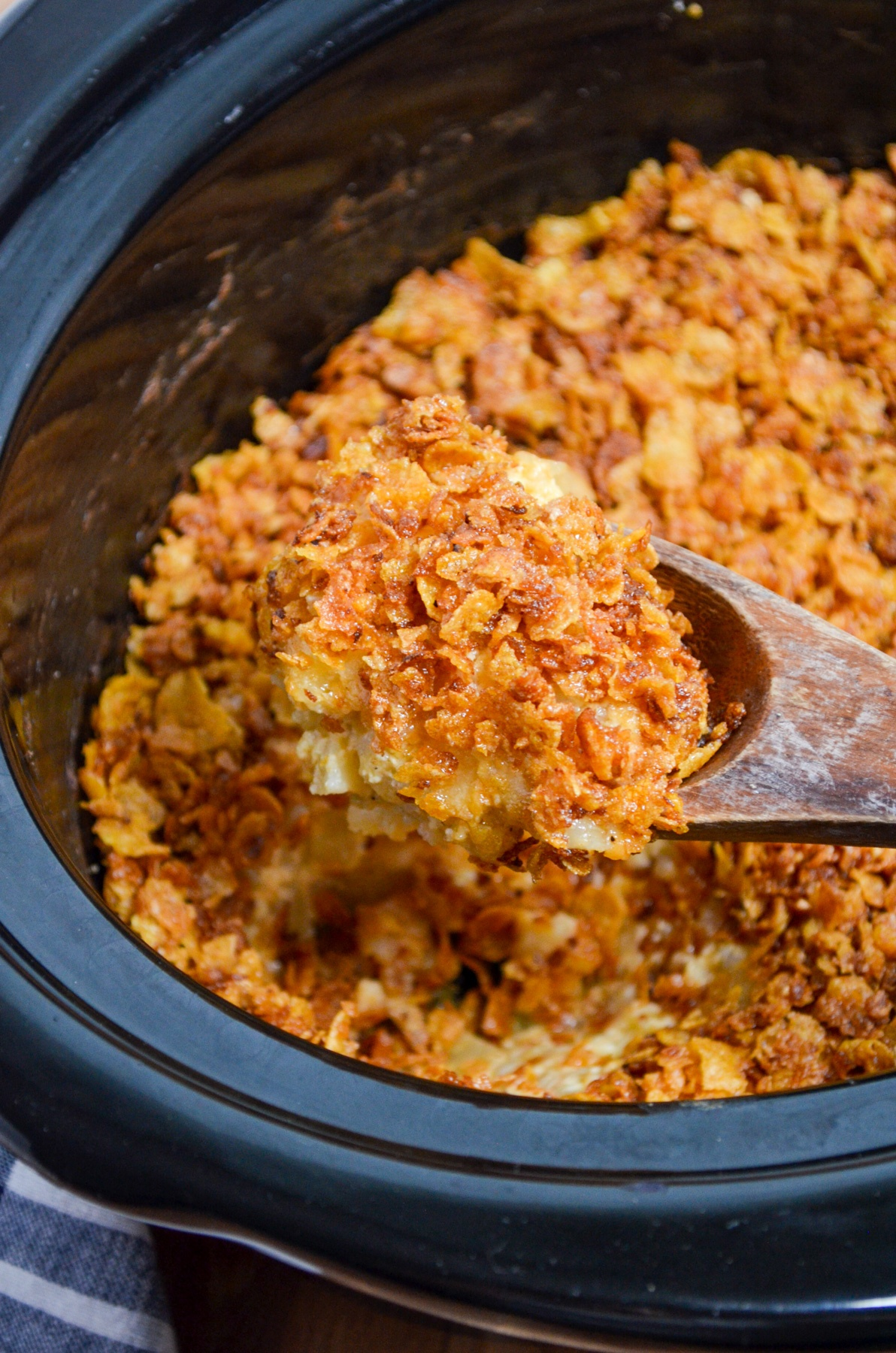 A wooden spoon picks up a portion of funeral potatoes from a crock pot.