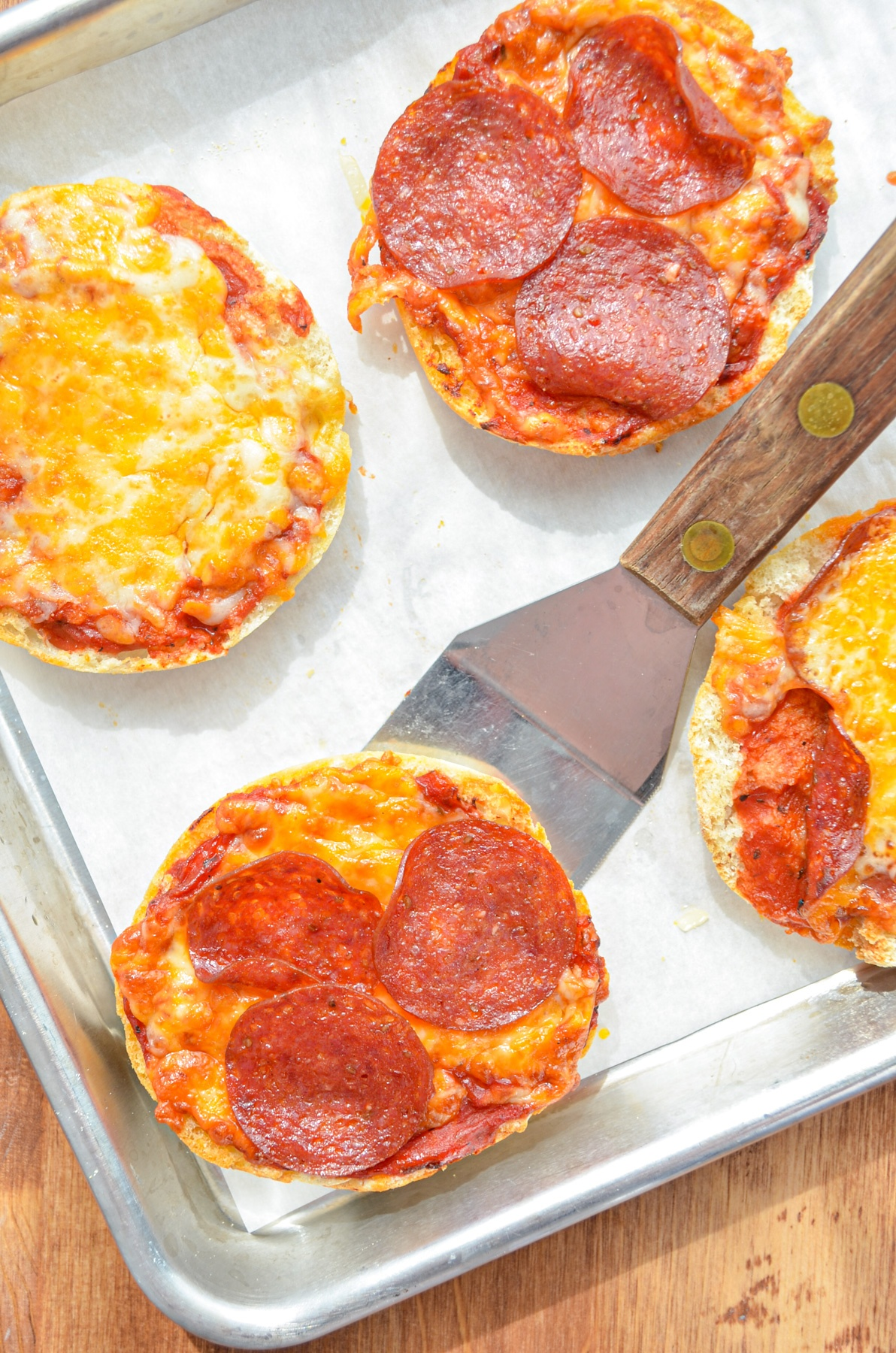 English muffin pizzas being lifted with a spatula.