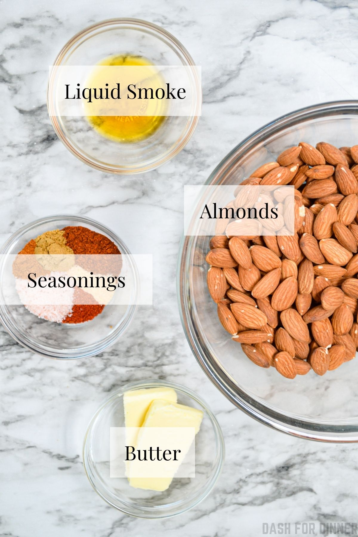 The ingredients needed to make roasted almonds: butter, almonds, liquid smoke, and butter.