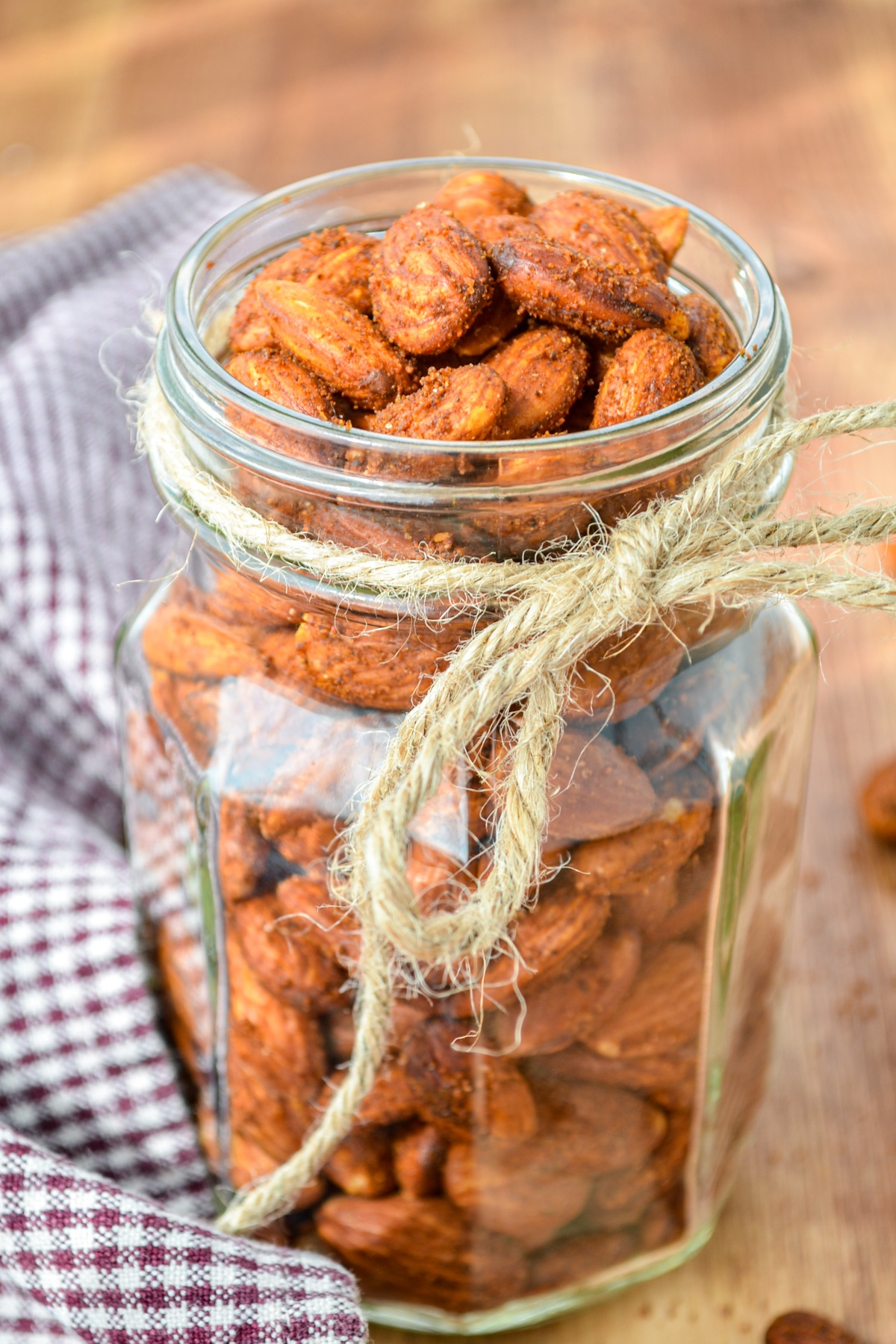 A fancy glass jar of roasted almonds, with a piece of twine tied around it.