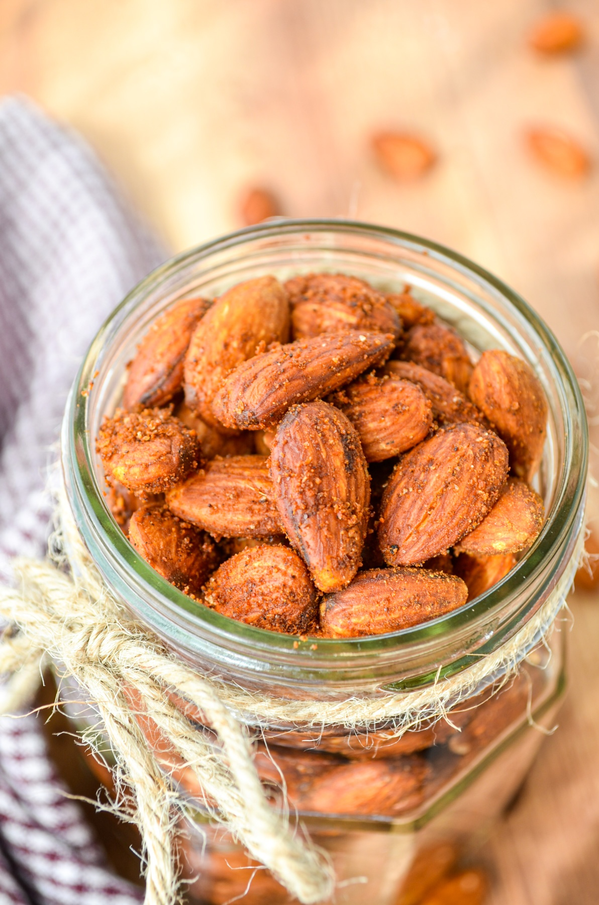 A jar full of roasted almonds, with a piece of twine tied around the rim.