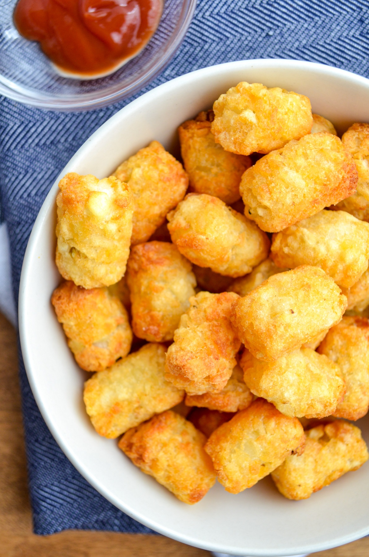 A bowl of tater tots, with a serving of ketchup on the side.