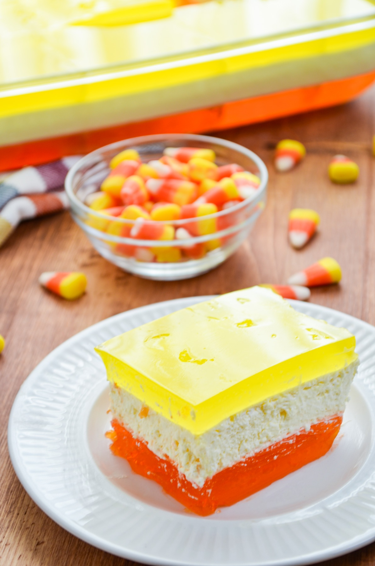 A slice of 3 layered halloween jello, with candy corns scattered in the background.