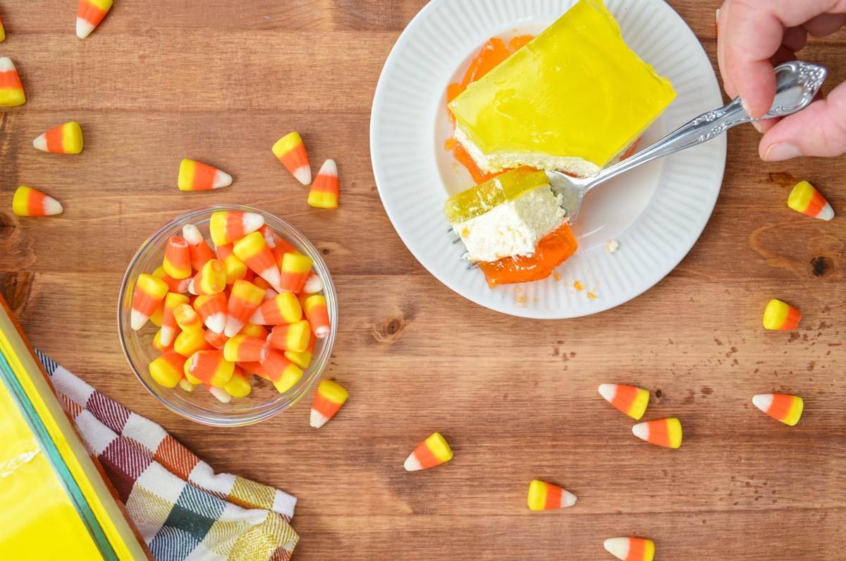 A layered lemon and orange jello dessert being cut into with a fork, a bowl of candy corn on the side.