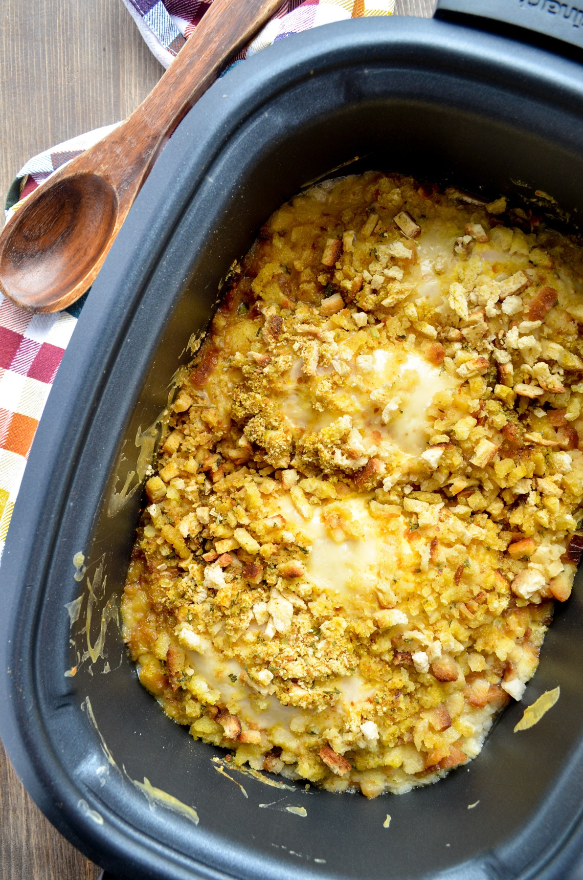A slow cooker on a wood table, with stuffing and swiss cheese coated chicken on the inside.
