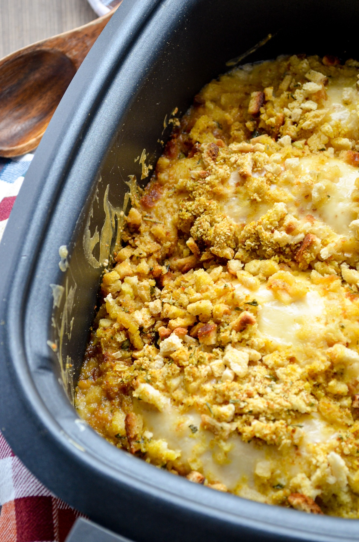 A slow cooker filled with stuffing and swiss cheese covered chicken breasts.